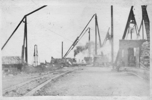 This photograph depicts the large number of derricks used in the dock area to load stone on the barges for shipment to Lake Erie ports such as Cleveland, Lorain, and Conneaut. The smoke in the center is from a Shays steam engine used to pull flatbed cars of stone. Note the two workmen on the center right hand side of the photo and the U. S. Flag on top of the upper right shed. Courtesy of M. Demattia.