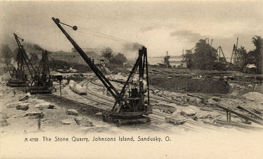 View of quarry with steam powered cranes used for loading limestone slabs on flatcars which were hauled to the dock area where the large derricks would load the slabs on barges for shipping. The cranes in this photo, which was taken about 90 years ago, are similar in basic design to modern-day cable cranes.