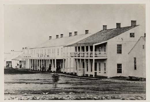 Union Officers Quarters partially showing Headquarters building on far right . Note what appears to be a woman and child walking in front of the first barracks building in the foreground.