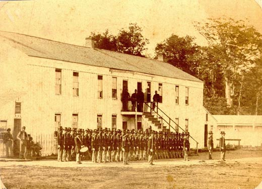 Company of the Hoffman Battalion at roll call. The barracks building was the same type built for the prisoners. The lean-to buildings on each end were kitchens. In the background is a portion of the stockade wall showing the parapet used by the guards while on duty. (Sandusky Library, Charles E. Frohman Collection).